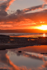 Beautiful cloud shapes and a bright orange sunset are reflected in the waters on the beach at Gisborne, New Zealand.