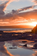 A striking orange sunset reflects in the rock pools at Gisborne, New Zealand.