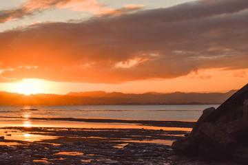 A pale orange sun sets above the calm beach in Gisborne, New Zealand.
