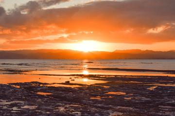 The setting orange sun reflects in the beach rock pools below in Gisborne, New Zealand.