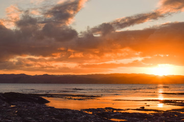 The pale sun sets in the background of the beach rock pools in Gisborne, New Zealand.