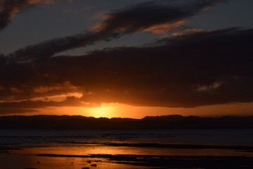The final glimpse of a orange sunset sandwiched between the night sky and dark hills in Gisborne, New Zealand.