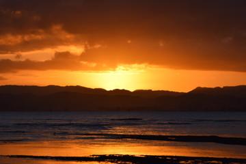 A bright orange sunset sky above the beach landscape in Gisborne, New Zealand.