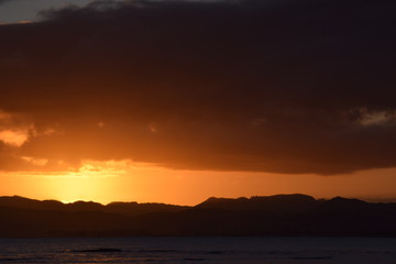 A dark hill l;andscape below the sinking orange sunset at Gisborne, New Zealand.