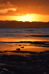A orange sun sets above the hills reflected in the sea water at Gisborne, New Zealand.