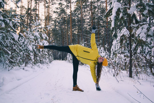 beautiful young woman in yellow jacket and hat doing workout or yoga in winter park among snow covered trees, healthy lifestyle
