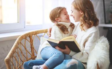 happy family mother reads book to child to daughter by window .