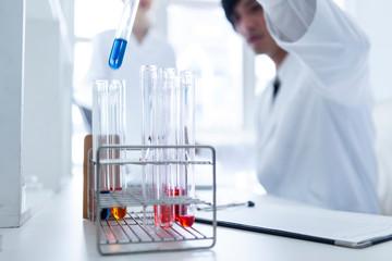 様々な色の液体が入った試験管を使い実験を行う科学者