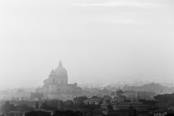 Moody view of S.M. degli Angeli church (Assisi, Umbria, Italy) in the midst of autumn mist