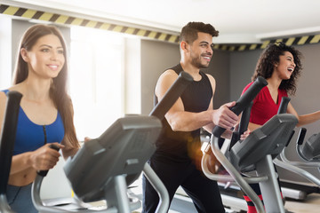 Young people exercising on cross-trainer in gym