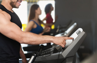 Sporty man adjusting speed on treadmill in gym