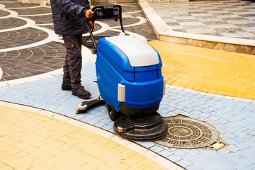 a man washes the street whith cleaning machine