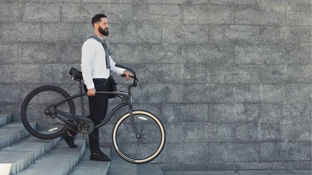 Handsome bearded businessman carrying his bicycle on stairs
