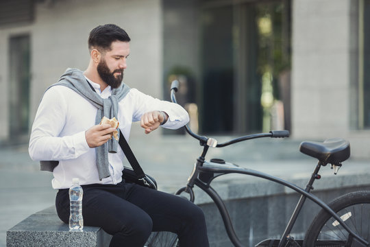 Businessman checking time on his watch eating lunch