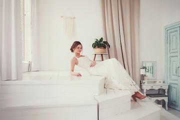 attractive bride posing in wedding dress in scandinavian interior