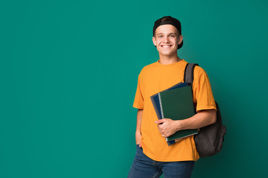 Teen guy with books and backpack over background