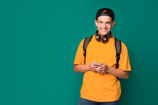 Teen guy texting on smartphone over turquoise background