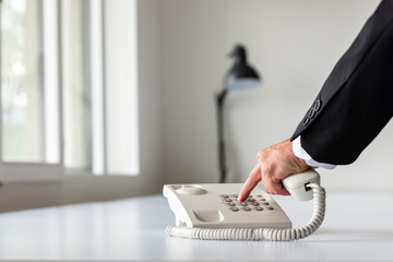 Businessman hand dialing a telephone number