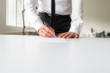 Businessman standing behind his office desk signing a document