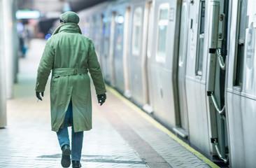 Afro american man at night entering subway train, back view