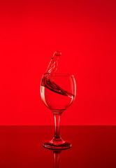 Splash of wine in a glass. Drink in glass on a red background.