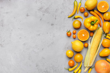 Collection of fresh yellow fruit and vegetables on gray background