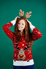 Woman in christmas clothes on green background