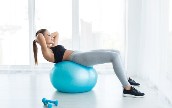 Woman working out with fitness ball in gym
