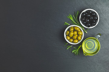 Set of black and green olives on plates, olive oil and rosemary on a black stone background