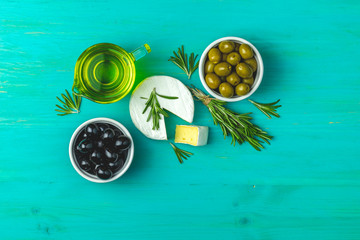 Cheese camembert, black and green olives, quail eggs on plates, olive oil and rosemary
