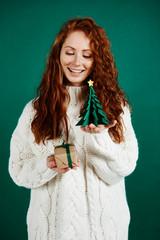 Shot of cheerful girl giving christmas present