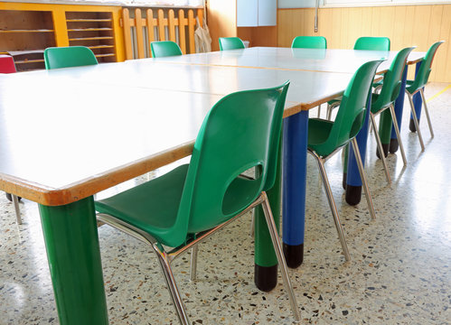 classroom of a school with green chairs and low tables suitable