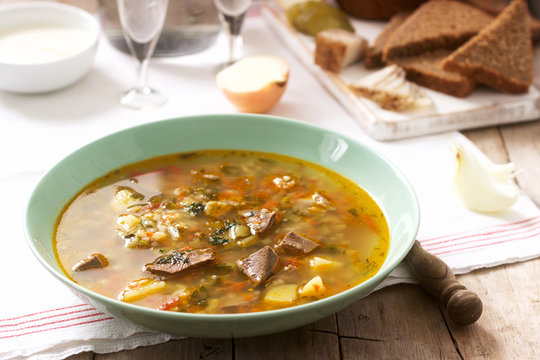 Rassolnik, traditional Russian soup, served with various snacks and vodka. Rustic style.