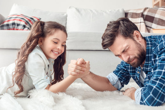 Father and little daughter at home lying on floor fighting playful