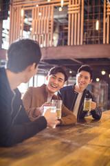 Happy young men drinking beer in bar