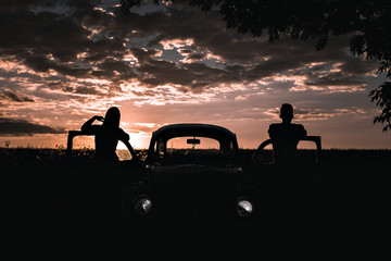 Silhouette of a couple with their car