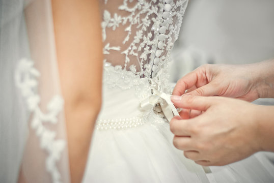 Wedding. Bridesmaid preparing bride for the wedding day. Bridesmaid helps fasten a wedding dress the bride before the ceremony. Luxury bridal dress close up. Best wedding morning. Wedding concept