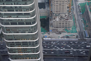 Cars drive past construction sites in Beijing's central business area