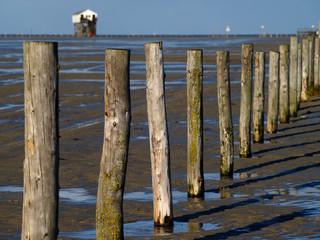 Holzpfähle am Strand, Pfahlbau im Hintergrund