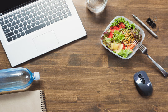 Healthy business lunch in office, salad, water on wooden table. Top view with copy space. Concept healthy nutrition. Lunchbox.