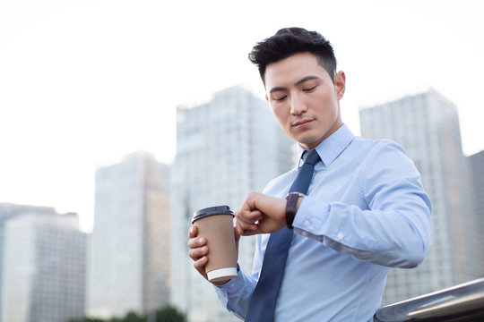 Confident young businessman checking the time