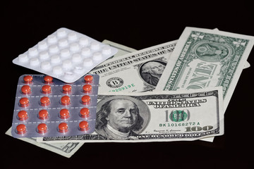 American dollars and pills blisters on black background