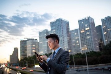 Young businessman using smartphone outdoors