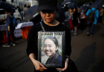 A woman holds a portrait picture of a relative, one of the 189 people killed in a Lion Air plane crash, during a rally in Jakarta