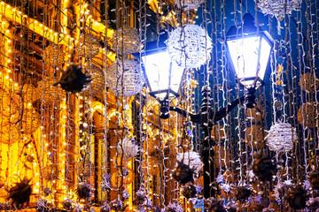 Christmas street decoration. Old lanterns and garlands, fabulous lighting.