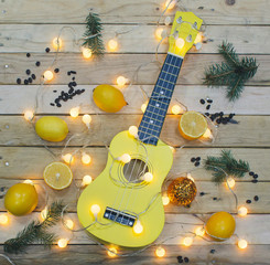 Photo shot, top view of yellow ukulele and Lemons on Wooden Background.