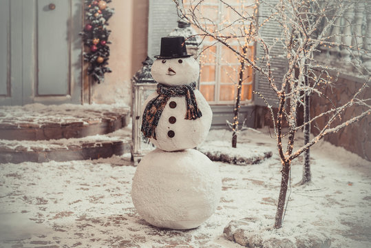 snowman in the yard is white in the evening on the background of the house New Year's yard Christmas landscape design winter magic snow joy