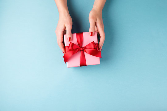 Overhead view on female hands with red manicure holding pink gift box  with red bow on blue background. Minimal styled composition.