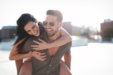 Happy young caucasian urban couple laughing and doing piggyback at outdoors