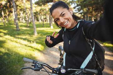 Attractive fit sportswoman riding on a bicycle at the park